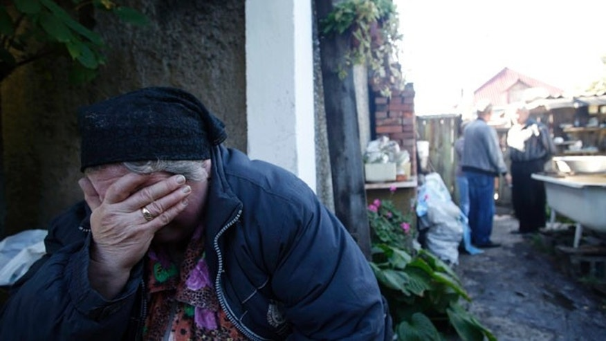 Sept. 19, 2014: Local resident Luba Zikova cries in front of her damaged house after shelling in the town of Donetsk, eastern Ukraine.