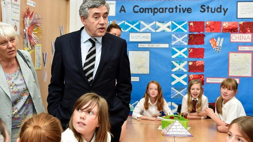 Former British Prime Minister Gordon Brown and NO campaigner in Scotland's Independence Referendum meets pupils at Kelty Primary school in Kelty Scotland Friday Sept. 19, 2014.  Voters in Scotland resoundingly rejected independence in a historic referendum that shook the country to its core.  But No does not mean a return to the status quo. The referendum led to promises of further powers for each of the four nations in the United Kingdom _ a pledge that will change the country forever.  (AP Photo/Garry F McHarg/PA) UNITED KINGDOM OUT