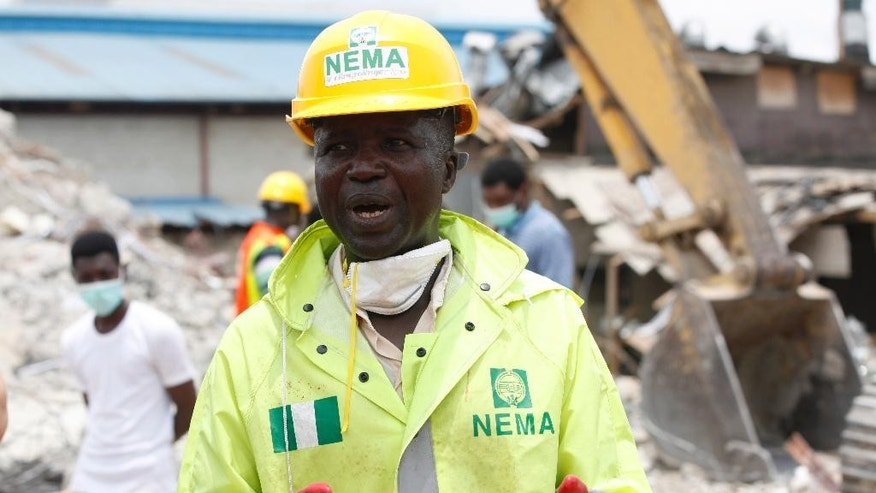 FILE- In this Wednesday, Sept. 17, 2014 file photo, Ibrahim Farinloye, spokesman for the Nigerian Emergency Management Agency, speaks on the rubble of a collapsed building belonging to the Synagogue Church of All Nations in Lagos, Nigeria. Lives were lost as church officials prevented workers from rescuing victims at the scene of a collapsed building in Lagos, Nigeria's emergency agency said Friday, Sept. 19, 2014. Most victims were South African, according to the South African government, which said at least 67 South Africans died and 17 appear missing in the rubble of the six-story building that had a shopping mall on the ground floor and guest rooms above. (AP Photo/Sunday Alamba, File)