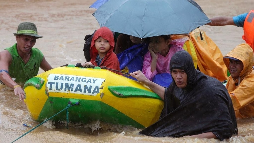Rescuers use a rubber dinghy to rescue trapped residents after heavy monsoon rains spawned by tropical storm Fung-Wong flooded Marikina city, east of Manila, Philippines and most parts of  the metropolis Friday, Sept. 19, 2014. Heavy rains due to a storm and the seasonal monsoon caused widespread flooding Friday in the Philippine capital and nearby provinces, shutting down schools and government offices. Local authorities reported thousands were evacuated early Friday from severely inundated communities, some under rapid-flowing flood waters more than neck high.(AP Photo/Bullit Marquez)