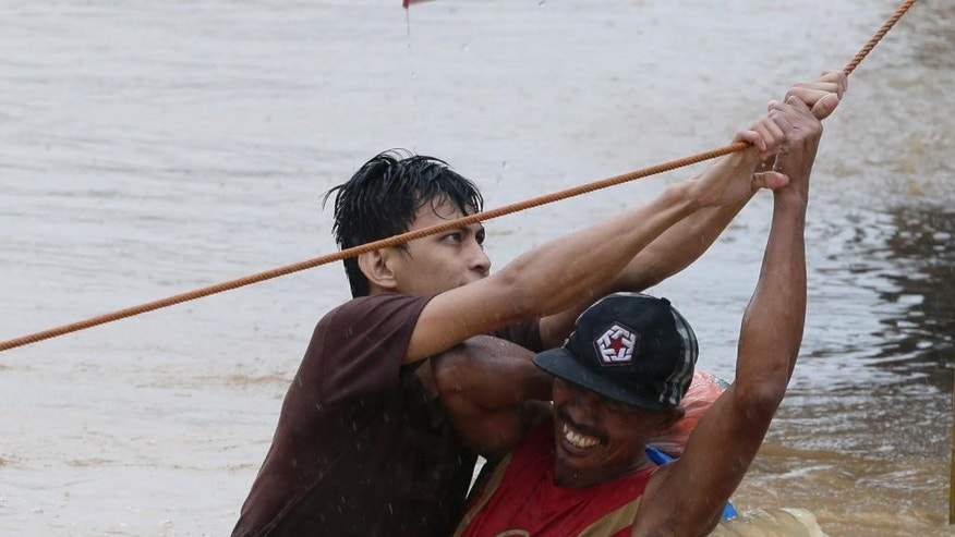 A rescuer helps a resident to go to a safer area after heavy monsoon rains spawned by tropical storm Fung-Wong flooded Marikina city, east of Manila, Philippines and most parts of the metropolis Friday, Sept. 19, 2014. Heavy rains due to a storm and the seasonal monsoon caused widespread flooding Friday in the Philippine capital and nearby provinces, shutting down schools and government offices. Local authorities reported thousands were evacuated early Friday from severely inundated communities, some under rapid-flowing flood waters more than neck high.(AP Photo/Bullit Marquez)