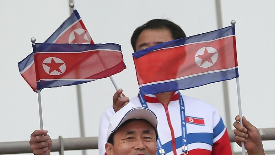 In this Sept. 18, 2014 photo, members of the North Korean delegation cheer their team during the men's first round Group F soccer match between North Korea and Pakistan at the 17th Asian Games at Hwaseong Sports Complex Main Stadium. North Korea is making a statement on the international sports stage — a fashion statement. With teams from 45 countries ready to roll after the games officially open Friday, the North's sportswear has already created something of a buzz in Incheon. (AP Photo/Eugene Hoshiko)