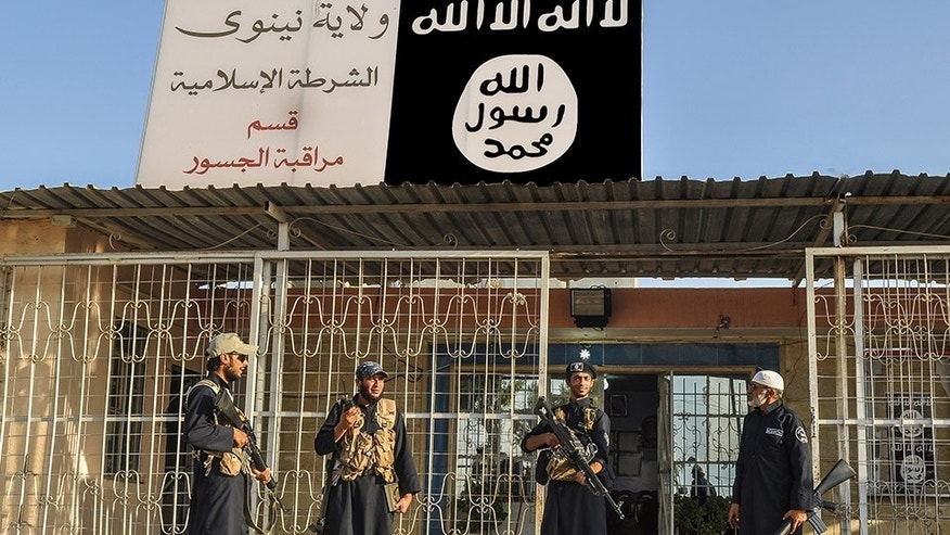 "This undated image posted on a militant website on Friday, Sept. 19, 2014, which has been verified and is consistent with other AP reporting, shows Islamic State group policemen standing guard in front of a police station in Nineveh province, Iraq. Arabic reads, ""Nineveh province, Islamic State police station, monitoring bridges department."" (AP Photo via militant website)"