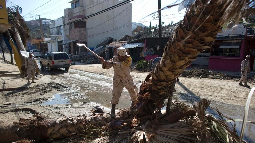 A Mexican army soldier uses an axe on a palm tree felled when Hurricane Odile made landfall as a Category 3 storm,  in Cabo San Lucas, Mexico, Thursday, Sept. 18, 2014. As clean up began, water and electricity service remained out and phone service intermittent. Electric commission officials said some 2,500 power poles were toppled by Odile, which struck late Sunday, leaving widespread damage and flooding. (AP Photo/Dario Lopez-Mills)