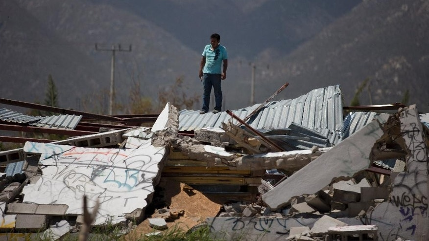 A man stands on top of a collapsed warehouse, looking for building material to salvage after Hurricane Odile destroyed his home, in San Jose de los Cabos, Mexico, Thursday, Sept. 18, 2014. Water and electricity service remained out and phone service was intermittent. Electric commission officials said some 2,500 power poles were toppled by Odile, which struck late Sunday as a Category 3 storm. (AP Photo/Dario Lopez-Mills)