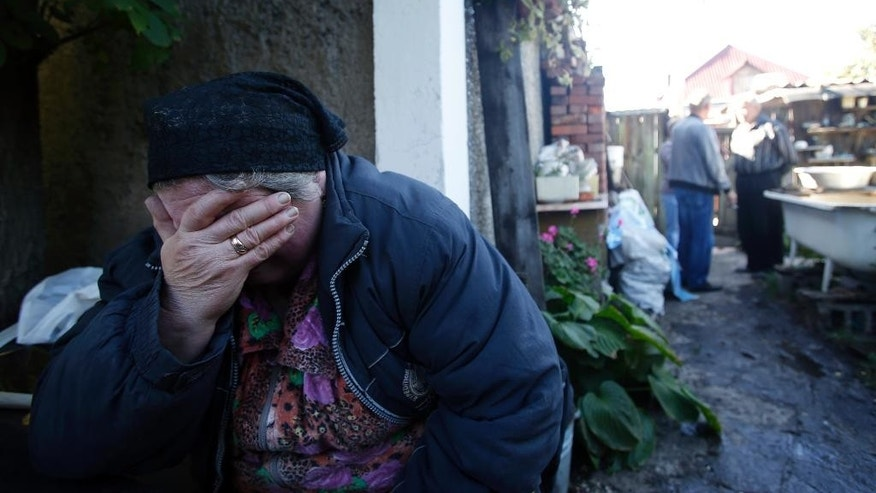 Local resident Luba Zikova cries in front of her damaged house after shelling in the town of Donetsk, eastern Ukraine, Friday, Sept. 19, 2014. One person was killed by overnight shelling in a neighborhood in the north of the city, where fighting centered around the government-held airport has spilled over into residential areas.(AP Photo/Darko Vojinovic)