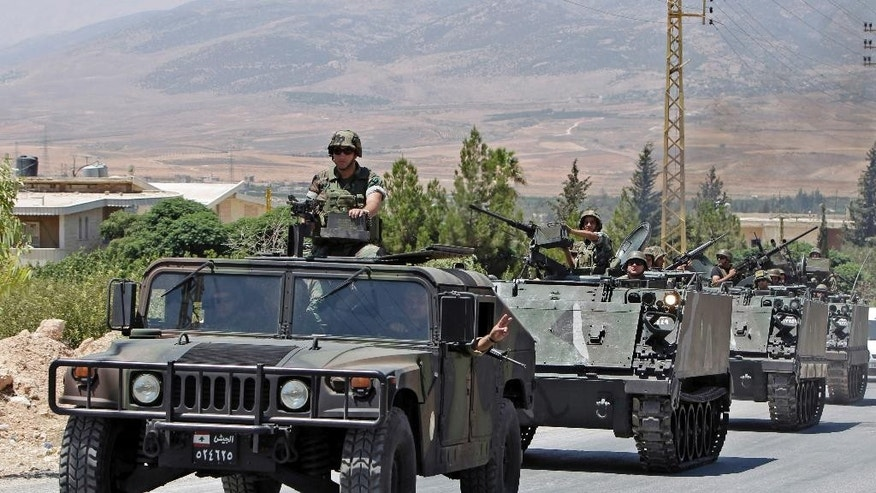 FILE -- In this Aug. 4, 2014, file photo, Lebanese army reinforcements arrive to the outskirts of Arsal, a predominantly Sunni Muslim town near the Syrian border in eastern Lebanon. Attackers blew up a roadside bomb near an army patrol near the Syrian border Friday, Sept. 19, 2014 killing two soldiers and wounding many in the latest spillover from the civil war next door, security official said. (AP Photo/Bilal Hussein, File)