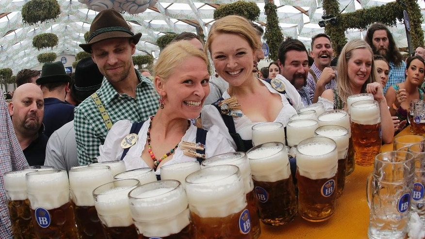 Waitresses Beli, right, and Anika pose with beer mugs during the opening of the 181th Oktoberfest beer festival in Munich, southern Germany, Saturday, Sept. 20, 2014. The world's largest beer festival will be held from Sept. 20 to Oct. 5, 2014. (AP Photo/Matthias Schrader)