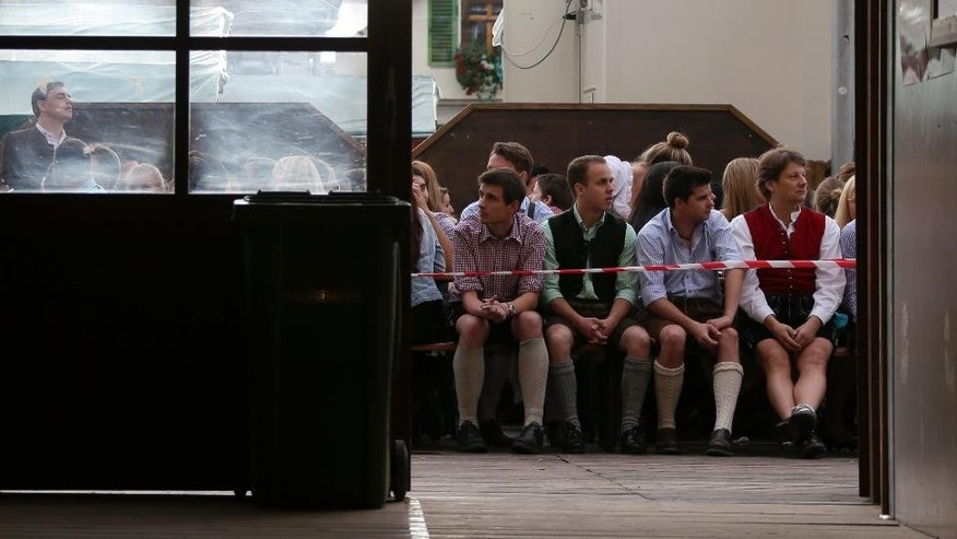 People await the opening of the 181th Oktoberfest beer festival in Munich, southern Germany, Saturday, Sept. 20, 2014. The world's largest beer festival will be held from Sept. 22 to Oct. 5, 2014. (AP Photo/Matthias Schrader)