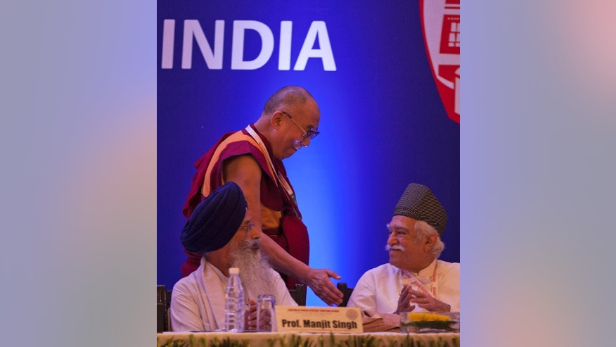 Tibetan spiritual leader the Dalai Lama, center, gently taps a participant as he walks back to his seat after delivering a speech during an inter-faith meeting in New Delhi, India, Saturday, Sept. 20, 2014. The Dalai Lama brought religious leaders together Saturday to mull some of India's most pressing problems, from gender violence to widespread poverty, while praising the country's religious harmony as proof to the world that different communities can live peacefully together. (AP Photo/Tsering Topgyal)