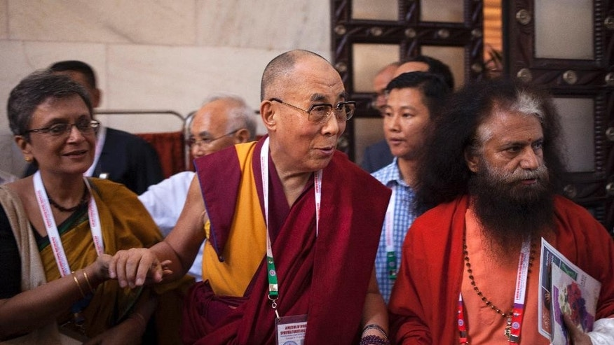 Tibetan spiritual leader the Dalai Lama, center, walks for a group photograph during an inter-faith meeting in New Delhi, India, Saturday, Sept. 20, 2014. The Dalai Lama brought religious leaders together Saturday to mull some of India's most pressing problems, from gender violence to widespread poverty, while praising the country's religious harmony as proof to the world that different communities can live peacefully together. (AP Photo/Tsering Topgyal)