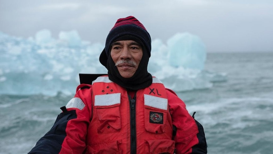 In this photo made available by Greenpeace International, President Anote Tong of the Pacific Island nation Kiribati in front of glacier ice from the retreating glacier Sveabreen on Svalbard. Norway. Fearing that his Pacific island nation could be swallowed by a rising ocean, the president of Kiribati says a visit to the melting Arctic has helped him appreciate the scale of the threat. President Anote Tong on Saturday, Sept. 20, 2014 ended a Greenpeace-organized tour of glaciers in Norway's Svalbard Archipelago, a trip he said left a deep impression that he would share with world leaders at a U.N. climate summit next week in New York. (AP Photo/Greenpeace International, Christian Aslund)