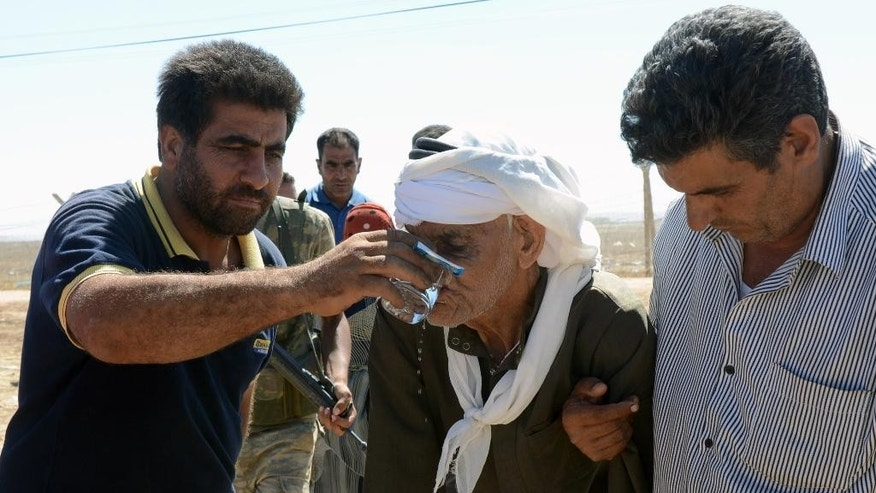 People offer water to a Syrian refugee at the border in Suruc, Turkey, Saturday, Sept. 20, 2014. Several thousand Syrians, most of them Kurds, crossed into Turkey on Friday to find refuge from Islamic State militants who have barreled through dozens of Kurdish villages in northern Syria in the past 48 hours. (AP Photo)