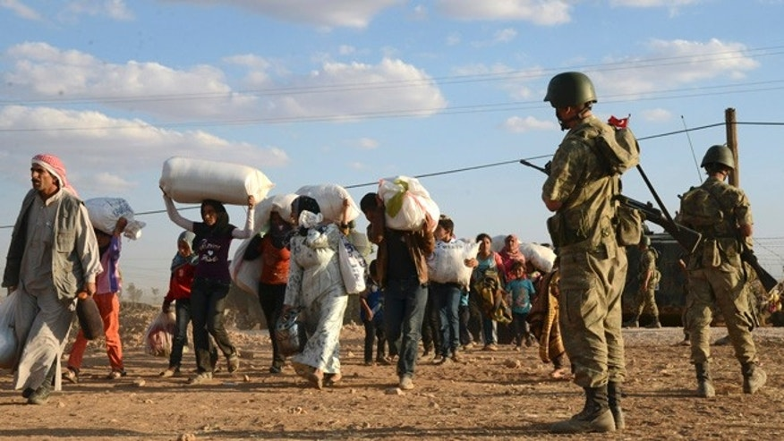 Sept. 20, 2014: Turkish soldiers stand guard as Syrian refugees gather at the border in Suruc, Turkey.