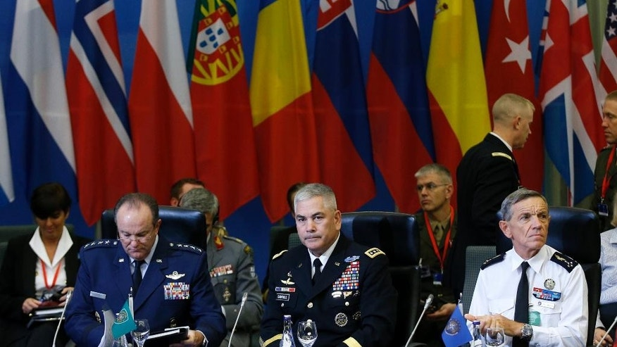 NATO's Supreme Allied Commander Europe (SACEUR) U.S. Gen. Philip M. Breedlove, left, U.S. Army Commander for International Security Assistance Force (ISAF), Gen. John F. Campbell, center, and NATO's Supreme Allied Commander Transformation (SACT) Gen. Jean-Paul Palomeros, right, attend a NATO Military Committee Conference in Vilnius, Lithuania, Saturday, Sept. 20, 2014.  (AP Photo/Mindaugas Kulbis)
