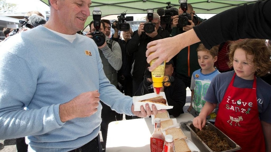 New Zealand Prime Minister and leader of the National Party John Key buys a sausage after casting his vote on the day of the national election in Auckland, New Zealand, Saturday, Sept. 20, 2014. Polls indicate Key's center-right National Party is the most popular party, and Key is the front-runner to remain the country's leader. (AP Photo/New Zealand Herald, Brett Phibbs) NEW ZEALAN OUT, AUSTRALIA OUT