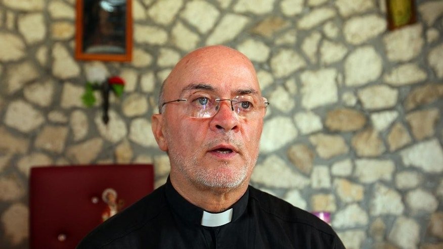 Father Carmine Leuzzi talks of the upcoming visit from Pope Francis, in the church of Shen Koll (Saint Nicholas) in Derven village, 32 kilometers (20 miles) north of capital Tirana, Thursday Sept. 18, 2014. The one-room, stone church of St. Nicholas, is particularly poignant: 15 Muslim families chipped in to help rebuild it in a sign of the remarkable coexistence that exists in Albania between Christians and Muslims. Pope Francis will highlight this interfaith harmony when he makes a one-day trip to the Balkan nation on Sunday, holding it up as a model for the Middle East and other parts of the world where Christians are being targeted by Islamic militants. (AP Photo/Hektor Pustina)