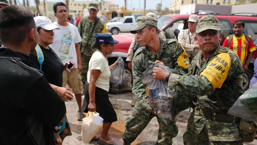 Soldiers distribute food and water to people outside the local Red Cross in the city of Cabo San Lucas, Mexico, Friday, Sept. 19, 2014. Most commerce in the city has halted after power and other utilities were knocked off by hurricane Odile. (AP Photo/Dario Lopez-Mills)