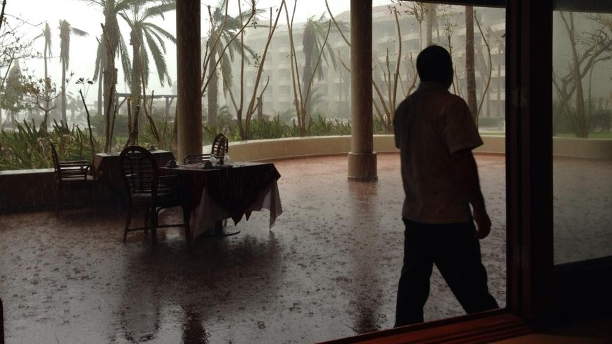 A waiter tries to get tables away from the rain at a hotel in San Jose de los Cabos, Mexico, Saturday, Sept. 20, 2014. Although Polo has degraded to a tropical storm, it is expected to drop up to 3 inches of rain on the southern tip of Baja, a region already devastated by hurricane Odile.  (AP Photo/Dario Lopez-Mills)