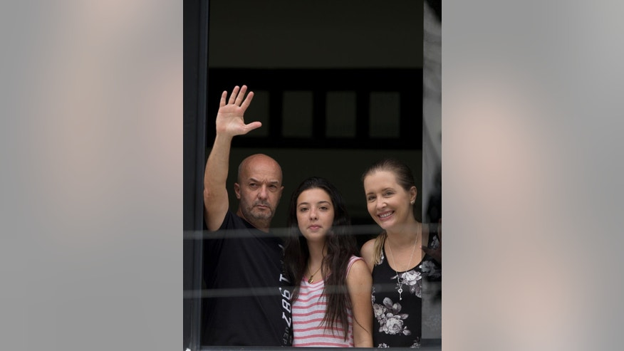 Ivan Simonovis, former Caracas police chief, left, waves to the media from the balcony of his home, accompanied by his daughter Ivana, center, and wife Bony, in Caracas, Venezuela, Saturday, Sept. 20, 2014. Simonovis whose decade-long imprisonment had rallied Venezuela's opposition has been released from jail on humanitarian grounds to continue serving a 30-year sentence at home. Simonovis had been jailed since 2004 in connection with the death of pro-government protesters who had rushed to the defense of then-President Hugo Chavez during a failed coup attempt two years earlier. In 2009, he was convicted of aggravated murder. (AP Photo/Fernando Llano)