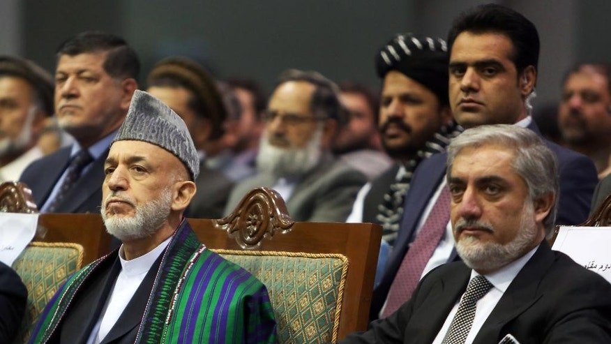 Afghan President Hamid Karzai, left, and Afghan presidential candidate Abdullah Abdullah attend a ceremony to mark the third anniversary of the assassination of former Afghan President Burhanuddin Rabbani in Kabul, Afghanistan, Saturday, Sept. 20, 2014. In 2011, an insurgent with a bomb wrapped in his turban assassinated Rabbani, who was leading a government effort to broker peace with the Taliban. (AP Photo/Rahmat Gul)