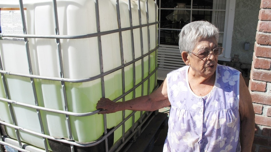 ** HOLD FOR MOVEMENT ** In this photo taken Monday, Sept. 15, 2014, Vickie Yorba, 94,  stands next to a water tank in front of her home in East Porterville, Calif., where she has lived for 66 years. Hers is one of 290 East Porterville wells that ran dry in the stateâs historic drought. Since February, she has had to rely on friends, relatives and charities for water to drink and bathe. (AP Photo/Scott Smith)