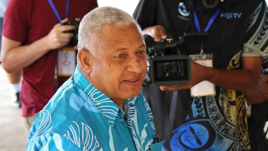 FILE - In this Sept. 17, 2014 file photo, Fiji's military ruler Voreqe Bainimarama arrives at a polling station to cast his vote in a national election in Suva, Fiji.  Official results Monday, Sept. 22, 2014,  from a landmark Fiji election confirm a big win for the nation's military ruler.  Bainimarama and his Fiji First party won an outright majority in the Parliament by taking 32 of 50 seats, according to results released by the Fijian Elections Office. (AP Photo/Pita Ligaiula, File)