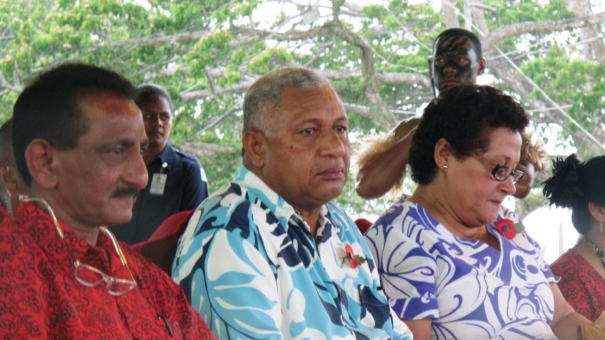 FILE - In this Nov. 7, 2013 file photo, Fiji's Prime Minister Voreqe Bainimarama, center, attends the opening of a picnic park in Suva, Fiji.  Official results Monday, Sept. 22, 2014,  from a landmark Fiji election confirm a big win for the nation's military ruler.  Bainimarama and his Fiji First party won an outright majority in the Parliament by taking 32 of 50 seats, according to results released by the Fijian Elections Office. (AP Photo/Nick Perry, File)