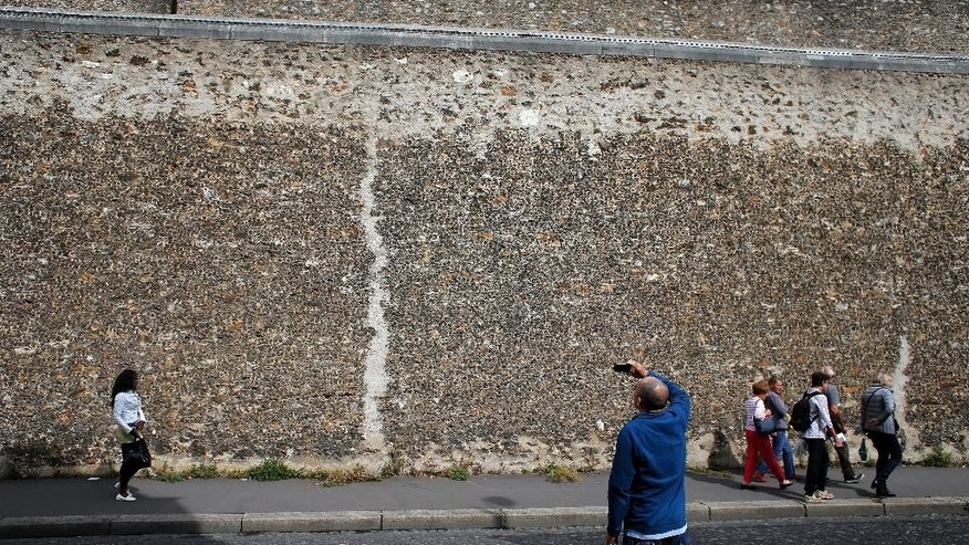 People walk along the wall of La Sante prison, in Paris, Sunday, Sept. 21, 2014. Paris' mythic La Santé prison opened its heavily guarded doors to visitors Sunday as part of the country's annual Heritage Days festival. Opened in 1867, the massive brown edifice in Paris' 14th arrondisement has held some of France's most notorious criminals, including international terrorist Carlos The Jackal, Nazi collaborator Maurice Papon, and rogue trader Jerome Kerviel. (AP Photo/Thibault Camus)