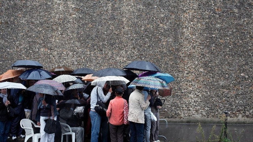 Visitors protect themselves from the rain with umbrellas prior to visiting La Sante prison, in Paris, Sunday, Sept. 21, 2014. Paris' mythic La Santé prison opened its heavily guarded doors to visitors Sunday as part of the country's annual Heritage Days festival. Opened in 1867, the massive brown edifice in Paris' 14th arrondisement has held some of France's most notorious criminals, including international terrorist Carlos The Jackal, Nazi collaborator Maurice Papon, and rogue trader Jerome Kerviel. (AP Photo/Thibault Camus)