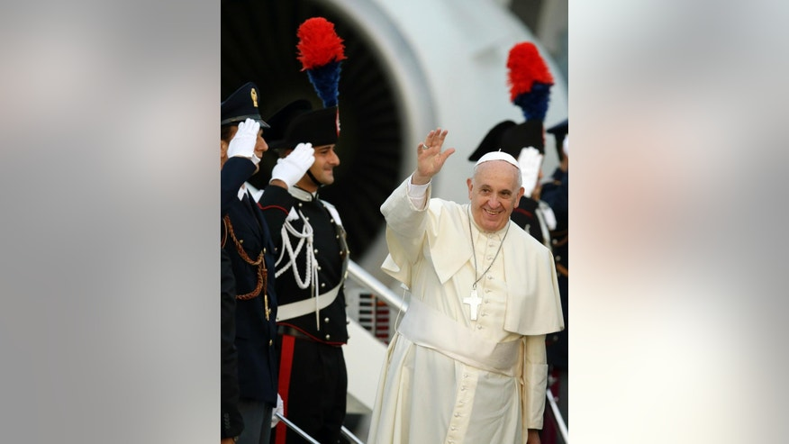 Pope Francis waves as he boards a plane on his way to Albania, at Rome's Fiumicino international airport, Sunday, Sept. 21, 2014. Pope Francis, who is traveling to Albania for a one-day trip, said he wanted to visit the country to highlight the rebirth of Christianity that was brutally wiped out during communist rule, and to showcase how Catholics, Orthodox and Muslims are working together now to govern the country. (AP Photo/Andrew Medichini)