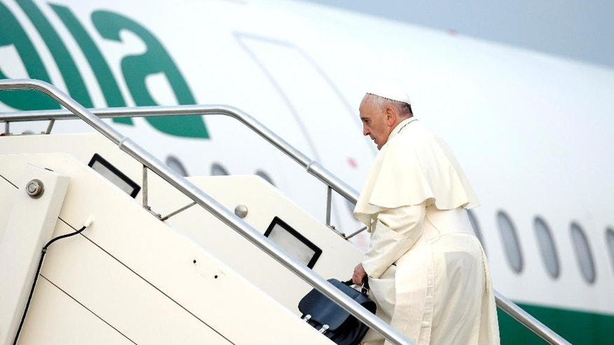 Pope Francis boards a plane on his way to Albania, at Rome's Fiumicino international airport, Sunday, Sept. 21, 2014. Pope Francis, who is traveling to Albania for a one-day trip, said he wanted to visit the country to highlight the rebirth of Christianity that was brutally wiped out during communist rule, and to showcase how Catholics, Orthodox and Muslims are working together now to govern the country. (AP Photo/Andrew Medichini)