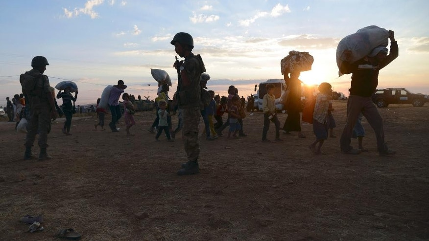 Turkish soldiers stand guard as Syrian refugees gather at the border in Suruc, Turkey, late Saturday, Sept. 20, 2014. Several thousand Syrians, most of them Kurds, crossed into Turkey on Friday to find refuge from Islamic State militants who have barreled through dozens of Kurdish villages in northern Syria in the past 48 hours.  (AP Photo)