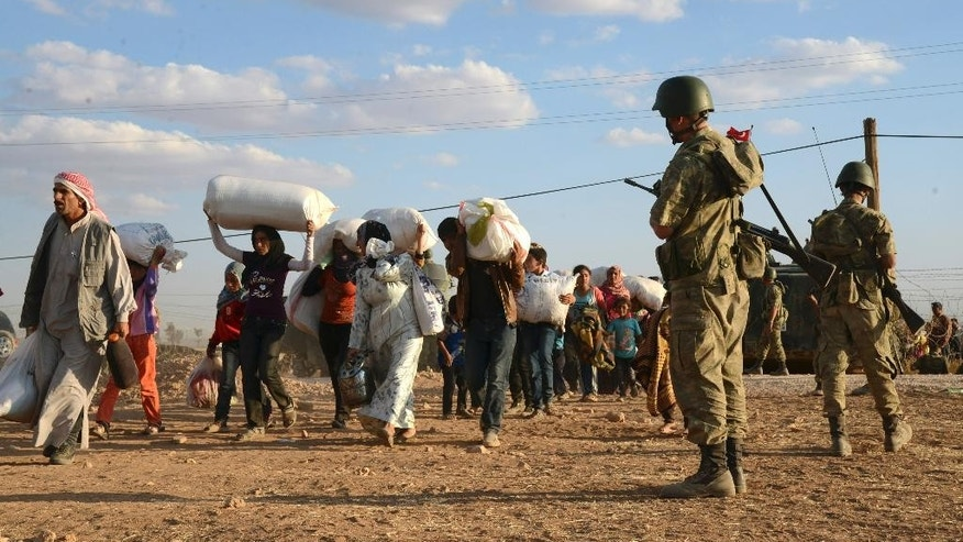 Turkish soldiers stand guard as Syrian refugees gather at the border in Suruc, Turkey, late Saturday, Sept. 20, 2014. Several thousand Syrians, most of them Kurds, crossed into Turkey on Friday to find refuge from Islamic State militants who have barreled through dozens of Kurdish villages in northern Syria in the past 48 hours.(AP Photo)