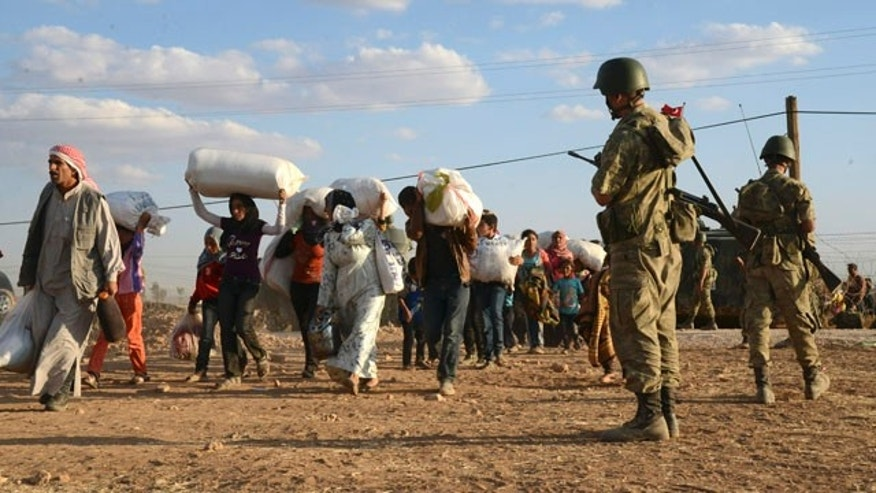 September 20, 2014: Turkish soldiers stand guard as Syrian refugees gather at the border in Suruc, Turkey.(AP Photo)