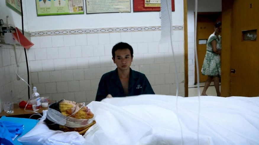 In this Monday, Sept. 22, 2014 photo, a man looks after his wounded relative at a hospital after an explosion at a fireworks factory in Liling in south China's Hunan province. An explosion at a fireworks factory in southern China killed at least 12 people and injured dozens of others, the local government said Tuesday.  (AP Photo) CHINA OUT