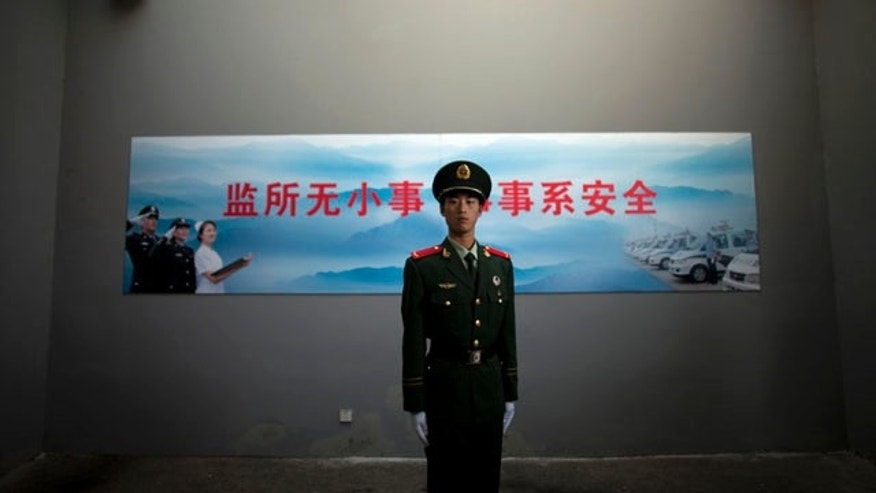 FILE - In this Oct. 25, 2012 file photo, a Chinese paramilitary policeman stands guard underneath a surveillance camera at an entrance to the Number Two Detention Center in Beijing, China. The slogan on the wall reads 'No small matter in detention center, everything concerns safety.' (AP Photo/Alexander F. Yuan, File)