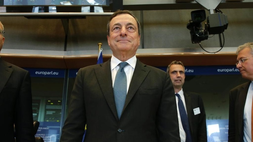 President of the European Central Bank Mario Draghi smiles before he takes his seat to address the Committee on Economic and Monetary Affairs, at the European Parliament building, in Brussels on Monday, Sept. 22, 2014. (AP Photo/Yves Logghe)