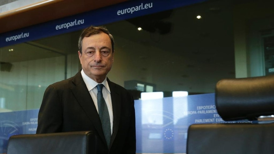 President of the European Central Bank Mario Draghi walks towards his seat to address the Committee on Economic and Monetary Affairs, at the European Parliament building, in Brussels on Monday, Sept. 22, 2014. (AP Photo/Yves Logghe)