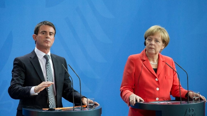German Chancellor Angela Merkel, right, and the Prime Minister of France, Manuel Valls, left, attend a press conference following their meeting at the chancellery in Berlin, Germany, Monday, Sept. 22, 2014. (AP Photo/Axel Schmidt)
