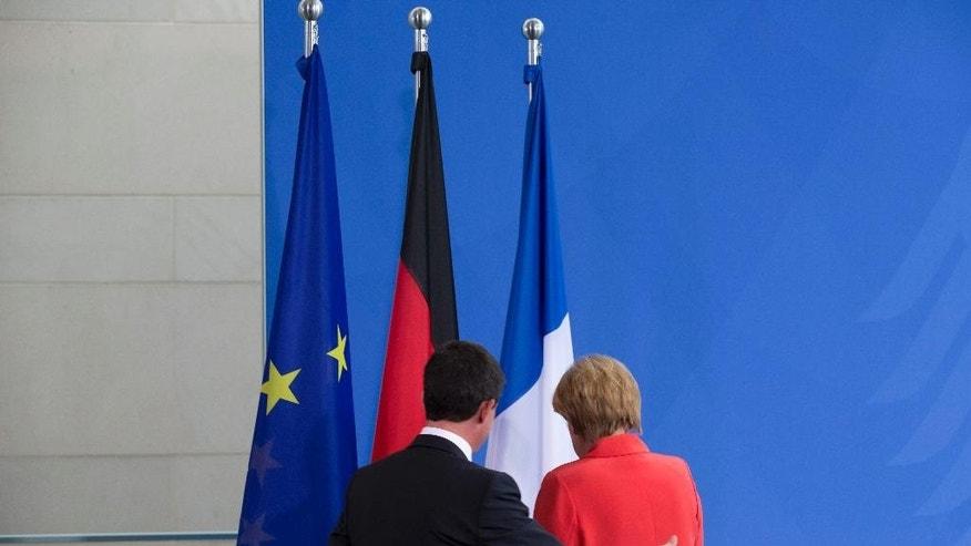 German Chancellor Angela Merkel, right, and the Prime Minister of France, Manuel Valls, left, leave a press conference following their meeting at the chancellery in Berlin, Germany, Monday, Sept. 22, 2014. (AP Photo/Axel Schmidt)