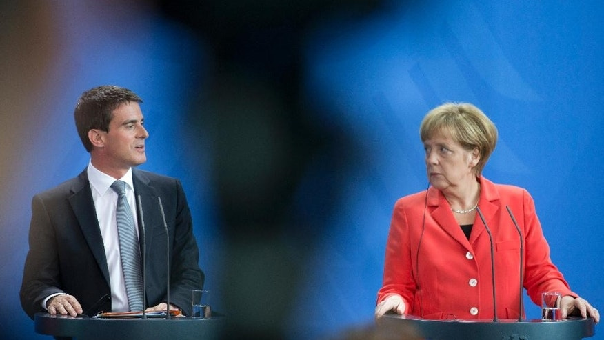 German Chancellor Angela Merkel, right, and Prime Minister of France Manuel Valls, left, attend a press conference following their meeting at the chancellery in Berlin, Germany, Monday, Sept. 22, 2014. (AP Photo/Axel Schmidt)