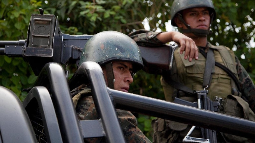 Soldiers patrol aboard an armed vehicle in San Juan Sacatepequez, Guatemala, Monday, Sept. 22, 2014. Guatemalan authorities have suspended some constitutional rights in San Juan Sacatepequez where 11 villagers died in a battle with guns and machetes on Friday night. The clash took place in the village of Pajoques between residents who support plans to build a cement factory and highway, and others who fear the construction could hurt their lands. (AP Photo/Moises Castillo)