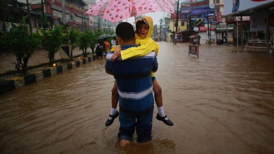 A man carrying his daughter wades through floodwaters in Gauhati, Assam state, India, Monday, Sept. 22, 2014. Officials say relentless rains in parts of northeastern India have triggered landslides and flash floods, killing at least seven people. (AP Photo/Anupam Nath)
