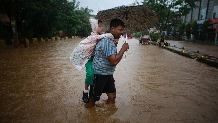 A man carrying his son on his back wades through floodwaters in Gauhati, Assam state, India, Monday, Sept. 22, 2014. Officials say relentless rains in parts of northeastern India have triggered landslides and flash floods, killing at least seven people. (AP Photo/Anupam Nath)