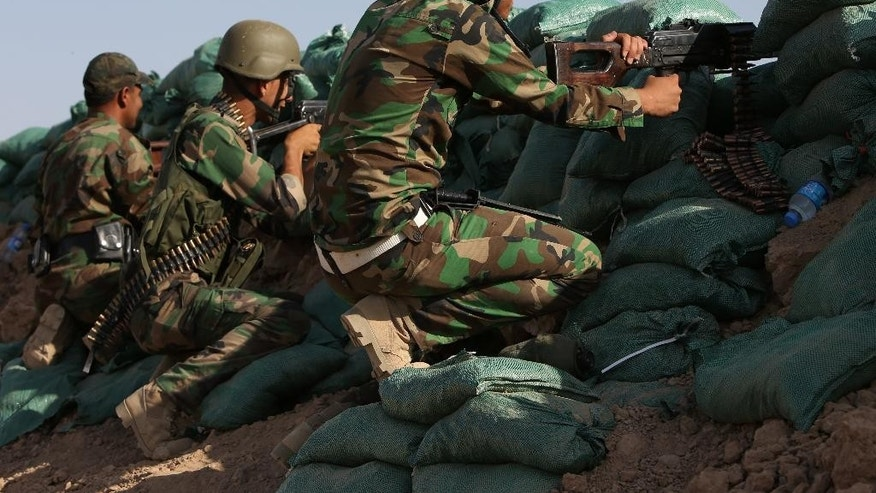 FILE - In this June 20, 2014, file photo, Kurdish peshmerga fighters takes their positions behind sand barriers at the village of Taza Khormato in the northern oil rich province of Kirkuk, Iraq. The insurgents came at midday, walking across a canal, advancing under cover of mortar fire toward the cluster of three Iraqi villages. Iraqi Kurdish forces have begun receiving training from western allies including the United States as they seek to beef up their capabilities against the Islamic State militant group, a top Kurdish security official said Monday, Sept. 22, 2014.(AP Photo/Hussein Malla, File)