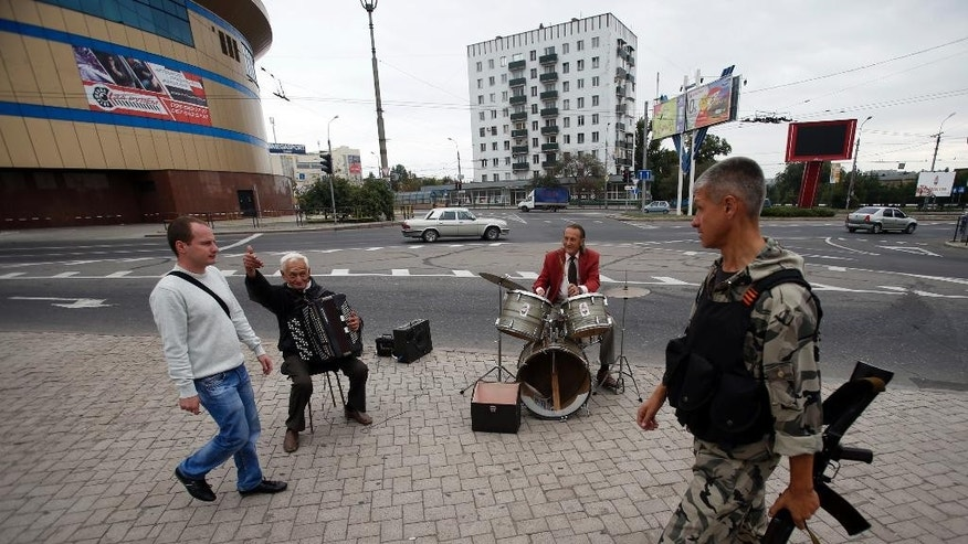 Street musicians perform in the town of Donetsk, eastern Ukraine, Monday, Sept. 22, 2014. A cease-fire was called on Sept. 5 but has been violated repeatedly. Negotiators from Ukraine, Russia, the rebels and the Organization for Security and Cooperation in Europe last week tried to further the peace process with an agreement calling for both sides to halt their advances and for pulling back heavy artillery in order to create a buffer zone. (AP Photo/Darko Vojinovic)