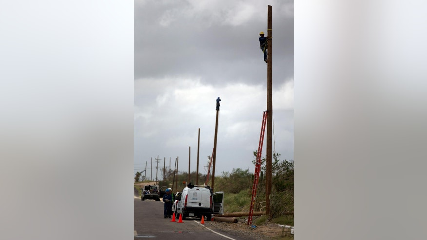 Workers of Mexico's Federal Electric Commission (CFE) work to raise new electrical utility poles in San Jose de los Cabos, Mexico, Saturday, Sept. 20, 2014. Six days after the passing of hurricane Odile, electrical power has yet to be restored. Mexico's President Pena Nieto has described the damage the storm caused to the electrical infrastructure as the worst in the history of the country's electrical commission. (AP Photo/Dario Lopez-Mills)