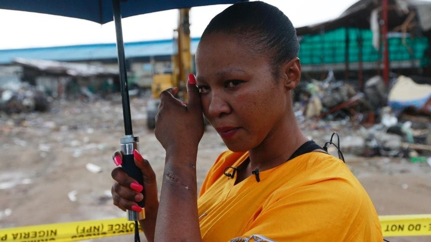 Lindiwe Ndwandwe, a 33 year old South African woman ,who spent five days under the rubble of a collapsed building belonging to the Synagogue Church of All Nations, before she was rescued, cries near the rubble, in Lagos, Nigeria, Saturday, 20. 2014. Lives were lost as church officials prevented workers from rescuing victims at the scene of a collapsed building in Lagos, Nigeria's emergency agency said Friday. Most victims were South African, according to the South African government, which said at least 67 South Africans died and 17 appear missing in the rubble of the six-story building that had a shopping mall on the ground floor and guest rooms above. (AP Photo/Sunday Alamba)