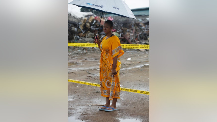 Lindiwe Ndwandwe, a 33 year old South African woman ,who spent five days under the rubble of a collapsed building belonging to the Synagogue Church of All Nations, before she was rescued, stands near the rubble in Lagos, Nigeria, Saturday, 20. 2014. Lives were lost as church officials prevented workers from rescuing victims at the scene of a collapsed building in Lagos, Nigeria's emergency agency said Friday. Most victims were South African, according to the South African government, which said at least 67 South Africans died and 17 appear missing in the rubble of the six-story building that had a shopping mall on the ground floor and guest rooms above. (AP Photo/Sunday Alamba)